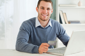 Male with credit card at his laptop
