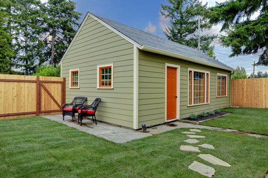 Small green and orange guest house in the back yard
