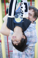 Active disabled five year old boy playing on the  monkey bars wi