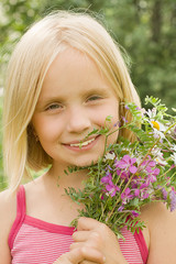 Smiling girl with flowers - happiness