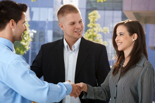 Businesspeople introducing outside of office
