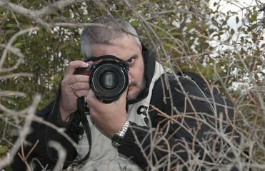Paparazzi escondido entre la vegetación.