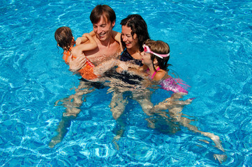 Happy family with kids in swimming pool. Summer vacation