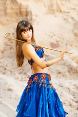 East belly dancer in blue lingerie with gold cane.