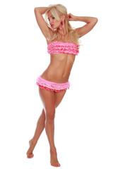 Beautiful model in pink bikini posing on a white background