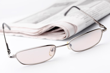 Eyeglass and newspaper