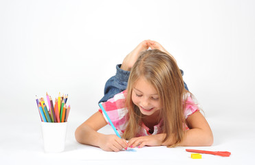 Little girl lying on floor and drawing, isolated on white