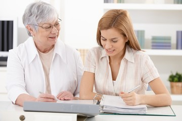 Mother and adult daughter doing paperwork