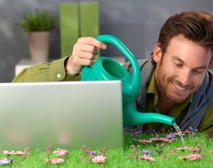 Cheerful man watering spring field table
