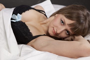 girl laying on bed wearing black lingerie