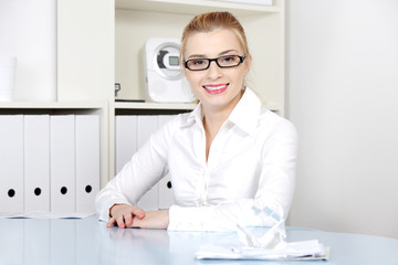 Smiling woman sitting behind the desk.