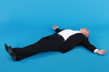 man lying against blue background