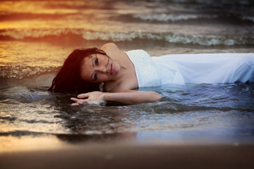 Young woman in wedding dress enjoys sea water during the sunset