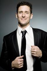 Handsome businessman in black suit expressing positivity.