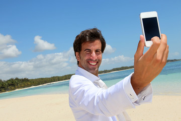 Groom taking picture of himself on a beach