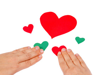 Hands combine red and green hearts on a white background