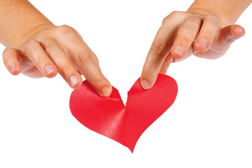 Hands tearing paper red heart on a white background