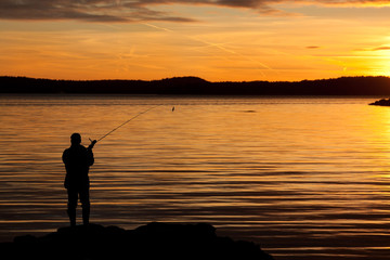 A fisherman in sunset at th acoast.