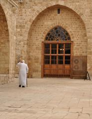 Old muslim men walking inside a mosque.