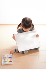 白い画用紙を持つ女の子