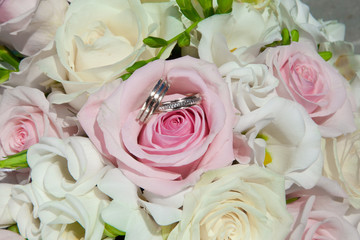 wedding rings on bouquet of bride