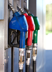 Three Colorful Pump Nozzles At The Gas Station