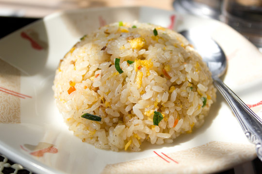 Round Chinese Fried Rice Served on a Dish with a Spoon Aside