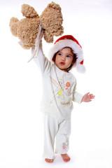 enfant en pijama et bonnet de noel montre son ours en peluche