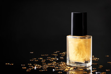 Golden nail polish on black background