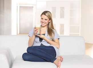 Young woman drinking coffee / latte macchiato
