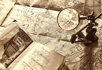 Old map and magnifying glass in sepia