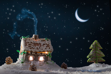 Snowy gingerbread cottage with stars at the lake