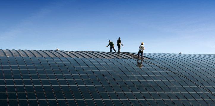Operai che installano pannelli solari sul tetto