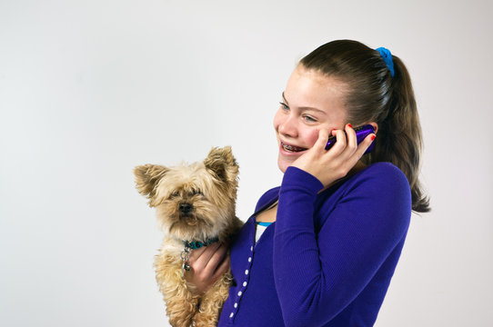 Teen girl talking on the phone holding a small dog