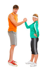 Fit girl and man in sportswear  shaking hands  isolated on white