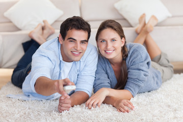 Smiling couple watching TV while lying on a carpet