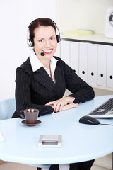 Beautiful business woman with headphones in office.