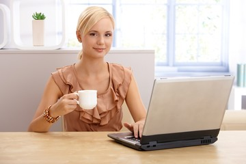 Young pretty woman with coffee and laptop
