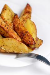 Жаренный картофель на белой тарелке с вилкой