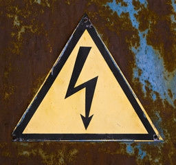 "sign ""high voltage"" on the background of rusted metal surface."