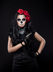 Serious woman in day of the dead mask with gun