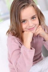 Portrait of cute little girl with hands on chin