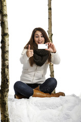 young woman in winter clothes taking a picture