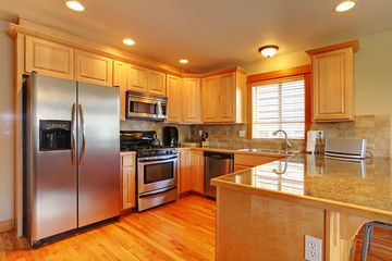 Golden maple cabinets kitchenw with new appliances.