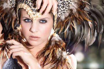 Junge Beauty Frau mit Federn Kopfputz blickt cool, quer