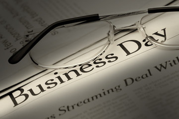 Eyeglasses lie on the newspaper with title Business day. Selecti
