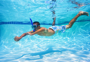 Young Man Swimming in Pool Underwater