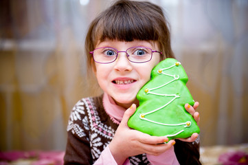 Portrait of smiling child girl with gingerbread