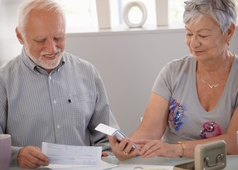 Elderly couple calculating budget