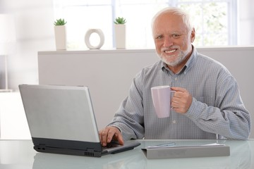 Mature man with computer smiling